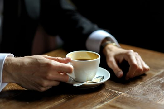 Groom's hands holding cup of coffee close-up