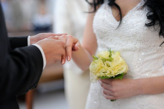 Groom is putting the ring on bride's finger