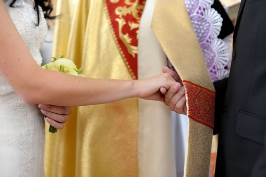 Bride and groom holding each other's hands while being blessed