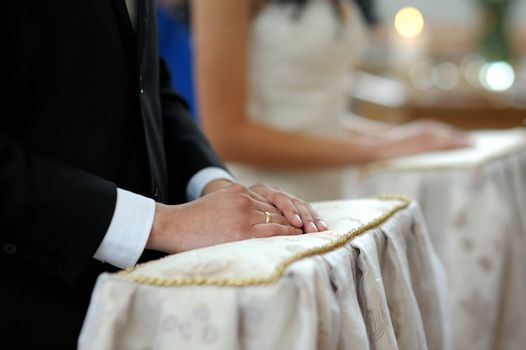Groom's hands on the pillow close-up during wedding church ceremony