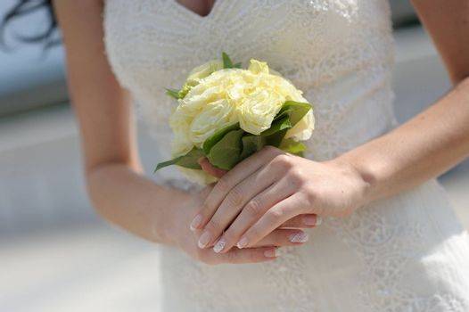 Nice bride's hands holding wedding bouquet of yellow roses against the white dress