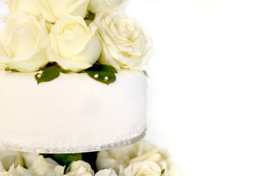 White cake with a bunch of yellow roses on the top