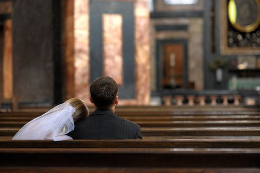 Bride and groom are sitting in the church
