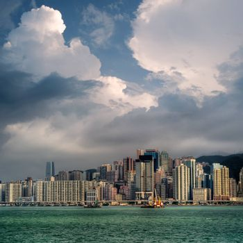 Cityscape with blue sky and white clouds near ocean in Hong Kong.