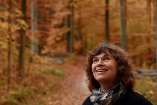 Mature woman in forest looking up at copyspace
