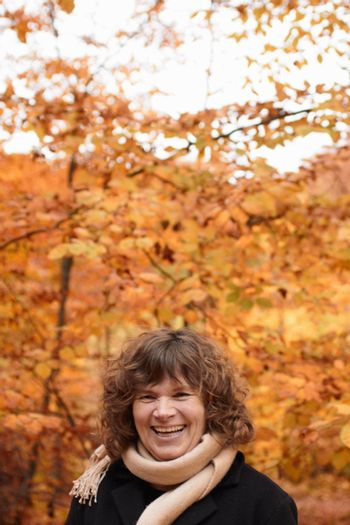 Autumn - happy middle aged woman laughing
