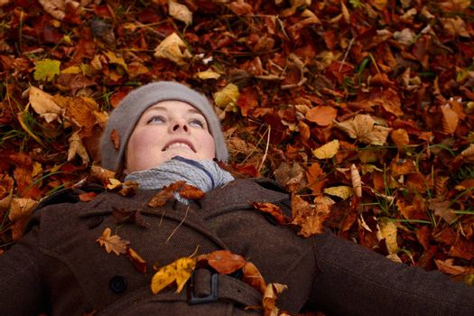 Fall - young woman lying down in leaves