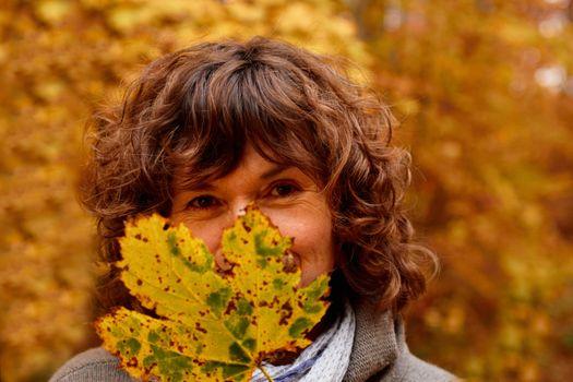 Mature woman hiding behind a  maple leaf