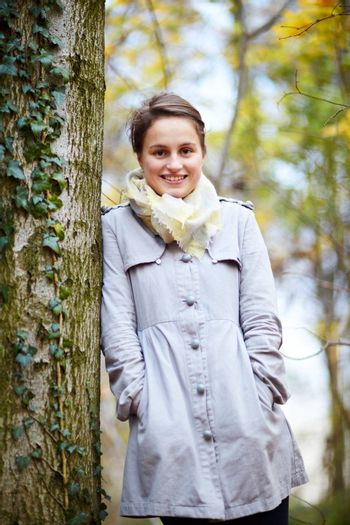 Trendy young woman standing beside a tree