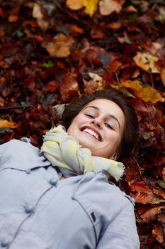 Smiling teenage girl lying in autumn leaves