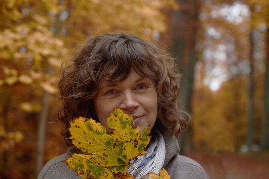 Autumn - middle aged woman looking at you behind a maple leaf