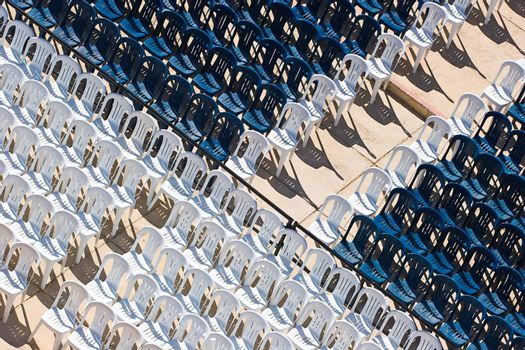 Rows of white and blue plastic chairs with no occupants
