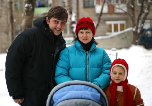 Father, mother, the daughter and newborn in stroller