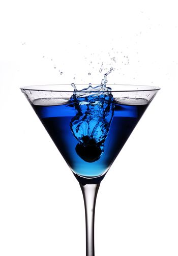 an olive being droped from height into a blue cocktail