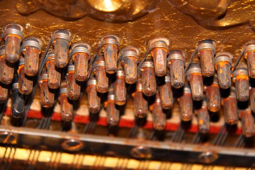 Inside an upright piano - tuning knobs and strings