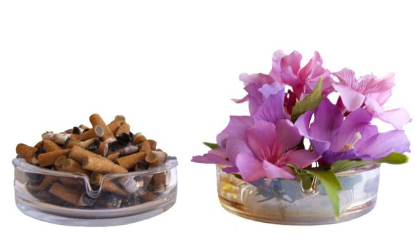 ashtray with two cigarette butts one another with flowers