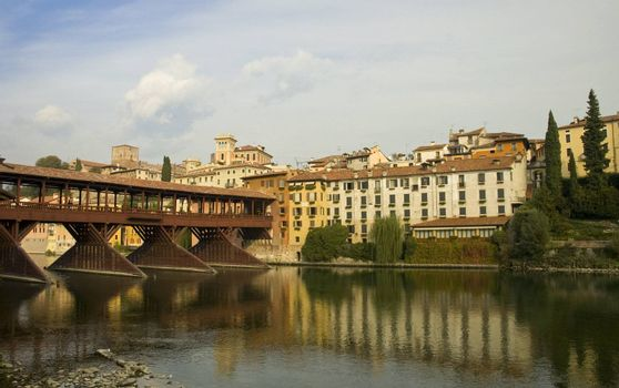 Bridge of Bassano del Grappa and houses that are reflected in the river
