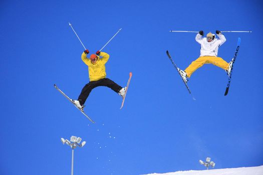 Two skiers performing stunts