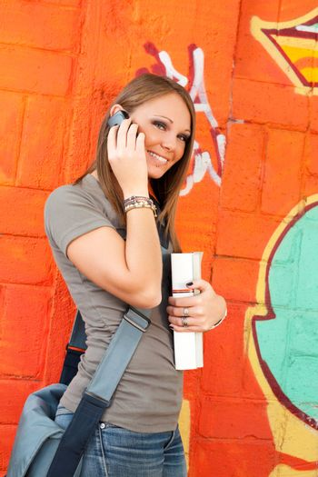 female college student on the phone looking at camera