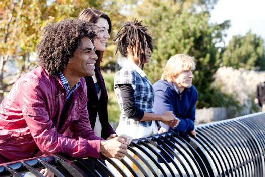 A group of friends outside in a park having fun - shallow depth of field with sharp focus on first person