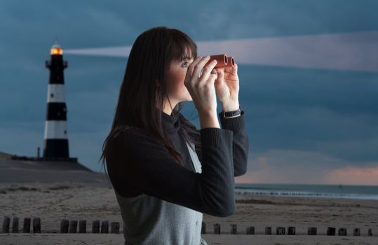 Brunette woman looking via binoculars; lighthouse on background