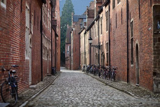 Bicycle leaned to a wall of brick medieval house; cobblestone pavement