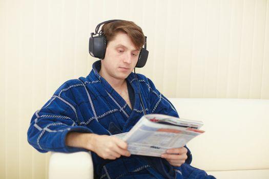 Man in big ear-phones on sofa reads journal