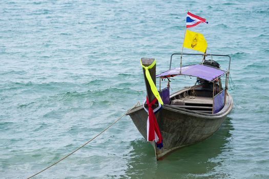 Traditional thai boat decorated with ribbons and flag