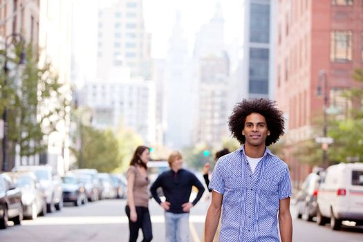 A city setting with a group of friends, a happy African American in the foreground