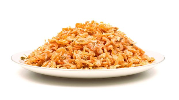Heap of dried shrimps on a white plate