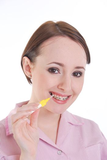 pretty girl with brace cleaning teeth