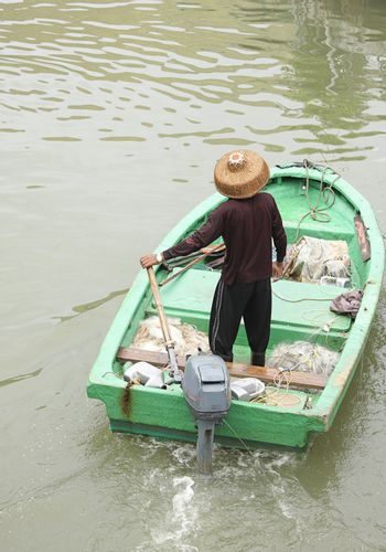 man on sampan boat with outboard motor