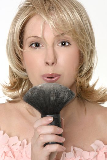Female flowing excess powder from makeup  brush