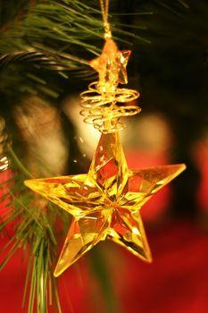 Golden star hanging on Christmas tree.