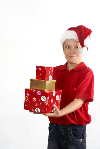 Child wearing red polo and jeans holding three gift boxes.