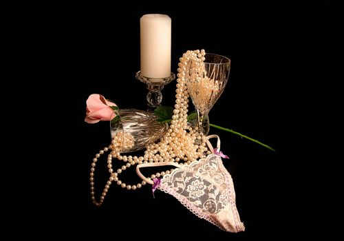 Romantic evening for two with candle, pink rose, pearls, wineglasses and lace.