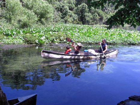 A family of three is kayaking in a springwater fed lake at a state park