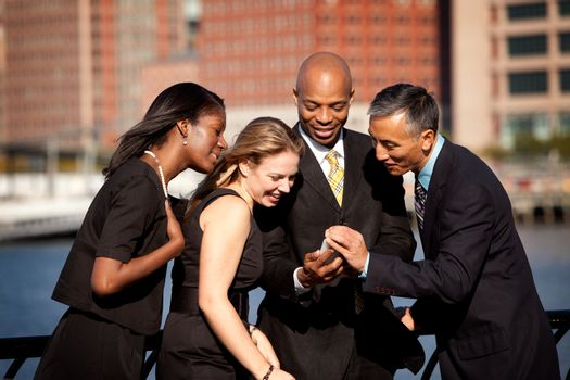 A group of business people crowded around a cell phone