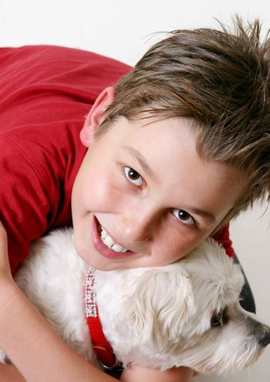 A boy cuddles a pet dog.