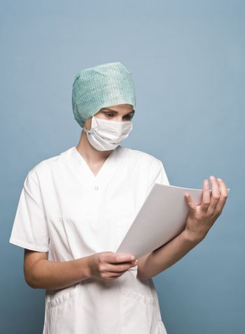 Nurse with surgical mask and a journal