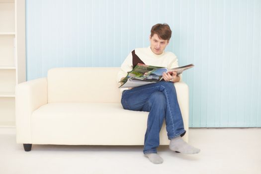 Young man sits on sofa with journal