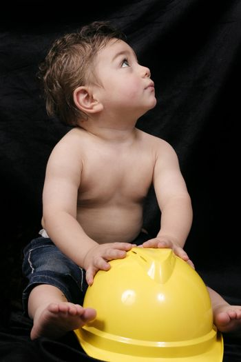 Young toddler plays with a bright yellow hardhat.
