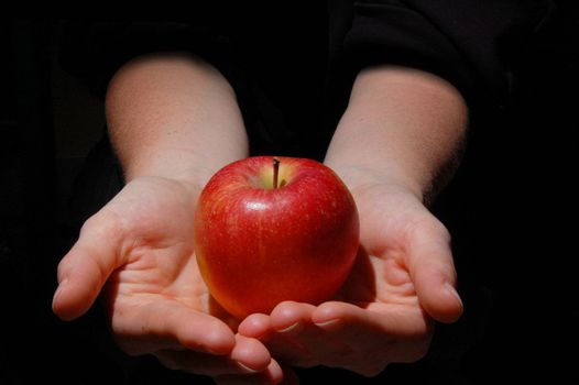 hand with red apple fruit on black background