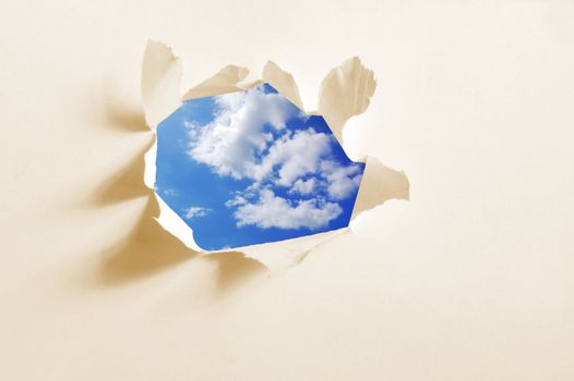 cloudy sky behind paper hole showing freedom