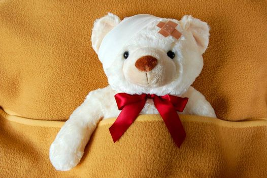 sick teddy bear in bed waiting for the doctor