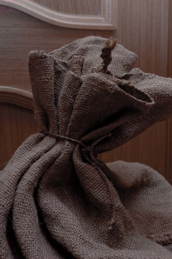 The top of a burlap bag tied by string