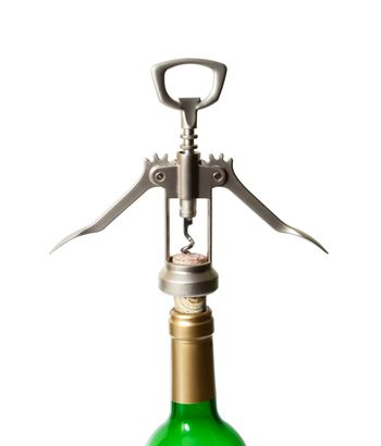 Corkscrew with extracted cork and a bottleneck isolated on white