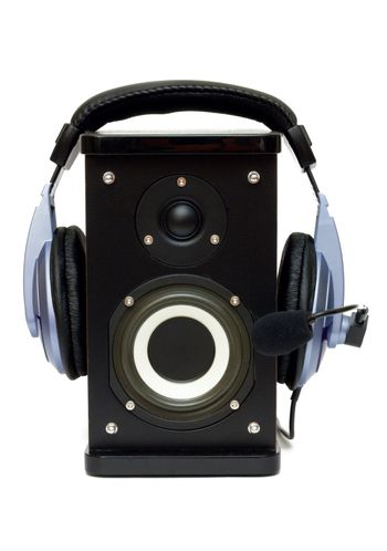 Headphones on a speaker isolated on white. Listening to music and playback.