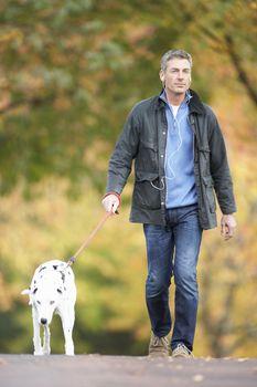 Man Walking Dog Through Autumn Park Listening to MP3 Player