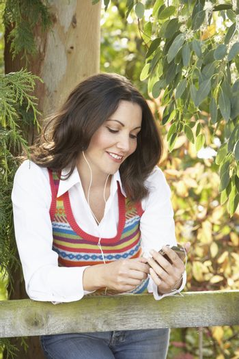 Young Woman Listening To MP3 Player Outdoors